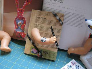 Using a doll arm as book closure